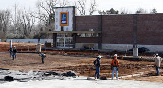 Workers construct drives and sidewalks around an ALDI grocery store being built on West Main Street, west of 24th Avenue NW, in Norman. PHOTO BY STEVE SISNEY, THE OKLAHOMAN STEVE SISNEY