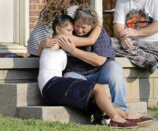 Lisa Kepler (left), 18, hugs Pam Wilkins on the steps of her home in Tulsa, the morning after Jeremey Lake was shot to death. Lisa Kepler was dating Lake, and her father, Officer Shannon Kepler, has been arrested in the fatal shooting outside of Wilkins' home Tuesday night. MICHAEL WYKE/Tulsa World