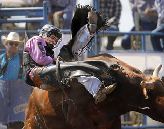 Wyatt Rogers, of Rose, fall from the bull during the bull riding event at the IFYR in the morning go-round on Monday at the Heart of Oklahoma Exposition Center in Shawnee. Photo by Jim Beckel, The Oklahoman