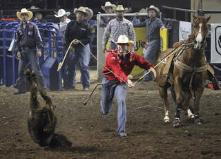 Tuf Cooper, of Decatur, Texas, participates in tie-down roping during the Ram National Circuit Finals Rodeo at the State Fair Arena in Oklahoma City, Saturday, March 31, 2012. Photo by Garett Fisbeck, For The Oklahoman
