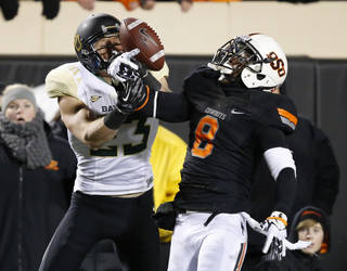 Oklahoma State safety Daytawion Lowe (8) breaks up a pass intended for Baylor wide receiver Clay Fuller (23) in the second quarter of an NCAA college football game in Stillwater, Okla., Saturday, Nov. 23, 2013. (AP Photo/Sue Ogrocki)