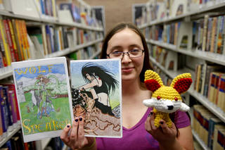 Southern Oaks Library art teacher Savannah Mitchell holds examples of entries in the Metropolitan Library System's Fan Fiction and Fan Art Contest. Photo by Bryan Terry, The Oklahoman