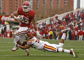 Oklahoma's Trey Millard (33) is brought down by Iowa State's Ter'Ran Benton (22) during a college football game between the University of Oklahoma Sooners (OU) and the Iowa State University Cyclones (ISU) at Gaylord Family-Oklahoma Memorial Stadium in Norman, Okla., Saturday, Nov. 26, 2011. Photo by Bryan Terry, The Oklahoman