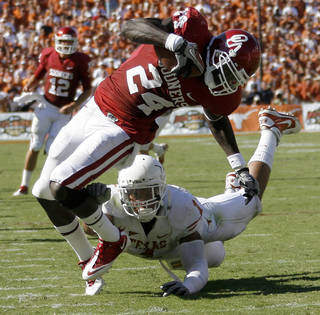 OU's Dejuan Miller fights of Keenan Robinson of Texas during the first half of the Red River Rivalry college football game between the University of Oklahoma Sooners (OU) and the University of Texas Longhorns (UT) at the Cotton Bowl on Saturday, Oct. 2, 2010, in Dallas, Texas. Photo by Bryan Terry, The Oklahoman