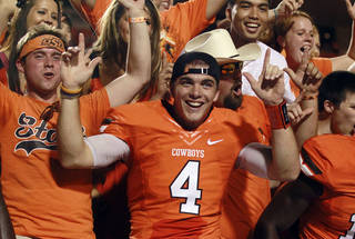 Oklahoma State quarterback J.W. Walsh (4) celebrates with fans following an 84-0 victory over Savannah State in an NCAA college football game in Stillwater, Okla., Saturday, Sept. 1, 2012. (AP Photo/Sue Ogrocki) ORG XMIT: OKSO112