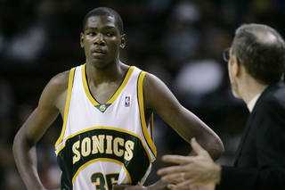 Seattle SuperSonics head coach P.J. Carlemiso, right, talks to rookie Kevin Durant during a time-out in an NBA exhibition basketball game Saturday, Oct. 20, 2007 at KeyArena in Seattle. (AP Photo/Ted S. Warren)
