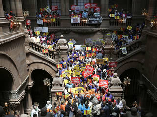 People rally Tuesday for an increase in the minimum wage on the Great Western Staircase at the state Capitol in Albany, N.Y. AP Photo Mike Groll -