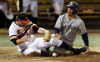 UC Irvine's Chris Rabago (22) slides home to score against OSU's Jon Perrin (46) in the 5th inning during Game 1 of the NCAA baseball Stillwater Super Regional between Oklahoma State and UC Irvine at Allie P. Reynolds Stadium in Stillwater, Okla., Friday, June 6, 2014. Photo by Nate Billings, The Oklahoman