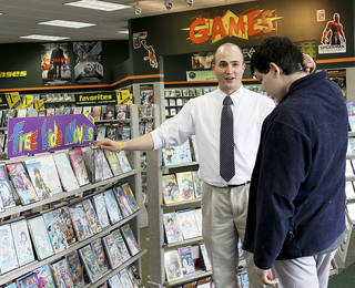 District Manager Tim O'Toole, 26, talks March 21 with a customer at Family Video store on N Western Avenue in Edmond. Photo by Tiffany Gibson, The Oklahoman