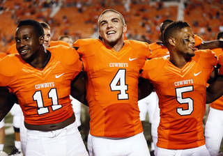 From left, Oklahoma State's Shaun Lewis, J.W. Walsh and Josh Stewart sing the alma mater after a college football game between the Oklahoma State University Cowboys (OSU) and the Lamar University Cardinals at Boone Pickens Stadium in Stillwater, Okla., Saturday, Sept. 14, 2013. OSU won, 59-3. Photo by Nate Billings, The Oklahoman