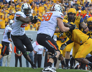 Oklahoma State running back Desmond Roland (5) eludes the West Virginia defense during the second quarter of an NCAA college football game in Morgantown, W.Va., on Saturday, Sept. 28, 2013. (AP Photo/Tyler Evert) ORG XMIT: WVTE101