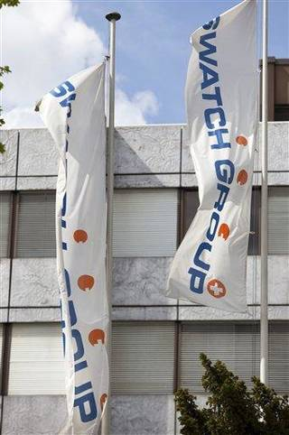 FILE - In this April 26, 2010 file picture flags wave in front of the headquarters of Swatch Group in Biel, Switzerland. Switzerland's biggest watch maker, Swatch Group AG, will pay about US dollar 1 billion to acquire Canada's Harry Winston watch and jewelry brand, officials from both companies said Monday, Jan. 14, 2013. (AP Photo/Keystone/Martin Ruetschi, File)