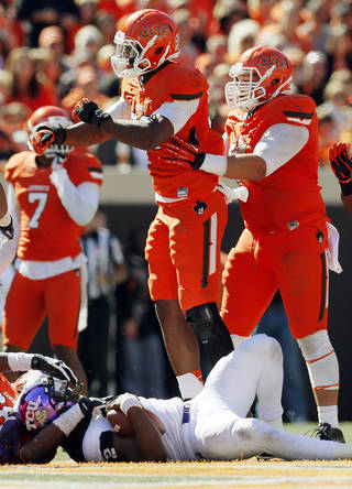 Oklahoma State's Jimmy Bean (92), middle, celebrates a sack of TCU's Trevone Boykin (2) with teammate James Castleman (91), right, during a college football game between the Oklahoma State University Cowboys (OSU) and the Texas Christian University Horned Frogs (TCU) at Boone Pickens Stadium in Stillwater, Okla., Saturday, Oct. 19, 2013. OSU won, 24-10. Photo by Nate Billings, The Oklahoman