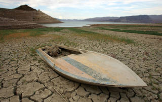 LAKE MEAD NRA, NV - JULY 26: A mud-covered boat is seen in an area that was until recently underwater July 26, 2007 in the Lake Mead National Recreation Area, Nevada. A seven-year drought and increased water demand spurred by explosive population growth in the Southwest has caused the water level at Lake Mead, which supplies water to Las Vegas, Arizona and Southern California, to drop over 100 feet to its lowest level since the 1960s. The National Park Service has been forced to close or extend boat launch ramps, and move entire marinas to try to keep up with the receding water levels. Because the water at the lake, the largest man-made reservoir in North America, isn't being replenished as fast as it's being used, water managers are now working to come up with plans to combat the effects of continued population growth, drought and a dwindling supply of water from the Colorado River due to climate change. (Photo by Ethan Miller/Getty Images)