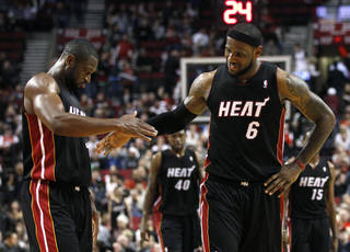 Miami Heat's Dwyane Wade and teammate Miami Heat's LeBron James (6) celebrate their victory following the NBA basketball game with the Portland Trail Blazers Thursday, March 1, 2012, in Portland, Ore. (AP Photo/Rick Bowmer) ORG XMIT: ORRB113