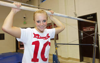 Kayla Nowak stands at the uneven bars on Monday during gymnastics practice at the University of Oklahoma. PHOTO BY DAVID MCDANIEL, THE OKLAHOMAN