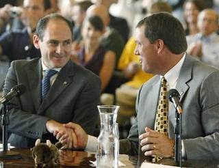 Pac-10 Commissioner Larry Scott, left, and University of Colorado Athletic Director Mike Bohn shake hands after Colorado's Board of Regents approved Colorado's joining the Pac-10 at a meeting in Boulder, Colo., on Friday, June 11, 2010. (AP Photo/Ed Andrieski)