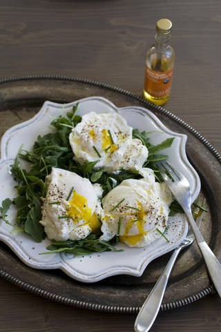 Poached eggs over ricotta cheese on arugula. MATTHEW MEAD - AP