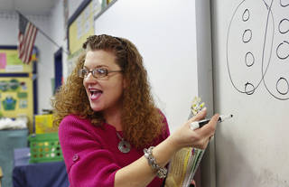 Sallie Harrison, a fourth-grade science and math teacher at Meeker Elementary School, explains long division to her students. Harrison has has multiple sclerosis. Photo by Jim Beckel, The Oklahoman Jim Beckel - THE OKLAHOMAN