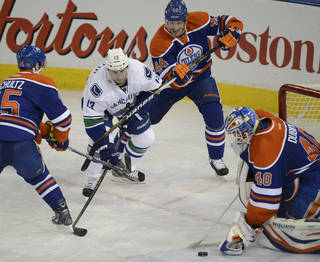 Edmonton Oilers goalie Devan Dubnyk stops the puck while the Vancouver Canucks' Steve Pinizzotto, 13 tries to get his stick on it during first period NHL hockey action in Edmonton, on Saturday, April 27, 2013. (AP Photo/The Canadian Press, Ian Jackson)