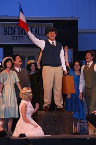 "George Bailey, played by Bryan Partridge, is surrounded by the people of Bedford Falls in Sooner Theatre's production of ""A Wonderful Life."" PHOTO PROVIDED"