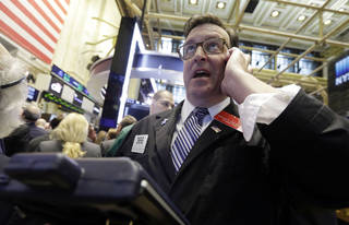 Trader Benedict Willis uses his mobile phone as he works on the floor of the New York Stock Exchange. AP Photo Richard Drew - AP