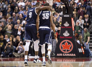 Oklahoma City Thunder forward Kevin Durant (35) is congratulated by teammate Serge Ibaka (9) after hitting a 3-point shot with 1.7 seconds left in the second overtime of an NBA basketball game agianst the Toronto Raptors in Toronto on Friday, March 21, 2014. The Thunder 119-118 in double overtime. (AP Photo/The Canadian Press, Nathan Denette)