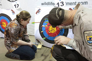 Delaney Rutledge, 11, South Rock Creek, Shawnee, has her target scored during the Oklahoma's National Archery in the Schools Program State Shoot in the Travel and Transportation Building at the State Fair Park, Wednesday, March 27, 2013. Photo By David McDaniel/The Oklahoman