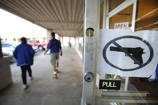 OPEN CARRY LAW: A no firearms sign hangs on the door at the Goodwill store at 15th and Broadway in Edmond, Monday November 19, 2012. Photo By Steve Gooch, The Oklahoman