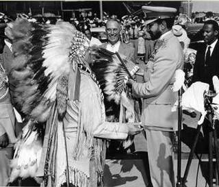 Haile Selassie, right, shakes the hand of a man in American Indian regalia in 1954 as Oklahoma A&M President Oliver Wilham watches. Photos provided.