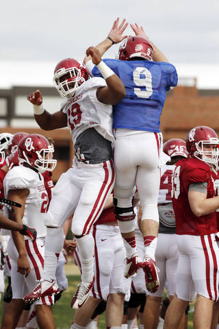 Linebacker Eric Striker (19) and quarterback Trevor Knight (9) jump and bump during Sooner spring football drills at University of Oklahoma (OU) on Tuesday, March 12, 2013 in Norman, Okla. Photo by Steve Sisney, The Oklahoman STEVE SISNEY