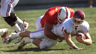 OU VS. LOUISVILLE FOOTBALL: Josh Heupel is sacked by #79 Donovan Arp.