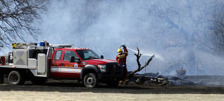 Above and below: Firemen put out a grass fire Thursday near SE 74 and S Pottawatomie Road in Oklahoma City. The fire burned across several acres. Photos by Steve Sisney, The Oklahoman STEVE SISNEY -
