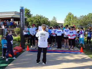 Janet Peery, CEO of YWCA Oklahoma City, addresses runners at the starting line before the organization's 2-Minute 5K race. PHOTO BY TIFFANY M. POOLE, THE OKLAHOMAN.