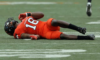 INJURED: Oklahoma State's Devin Hedgepeth (18) lies on the turf after an injury during a college football game between Oklahoma State University (OSU) and the University of Louisiana-Lafayette (ULL) at Boone Pickens Stadium in Stillwater, Okla., Saturday, Sept. 15, 2012. Photo by Sarah Phipps, The Oklahoman