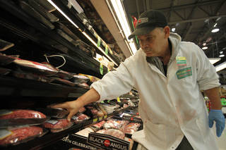 Francisco Ramirez, assistant meat manager, stocks the meat department at Buy For Less on NW Expressway. Aliki Dyer - The Oklahoman