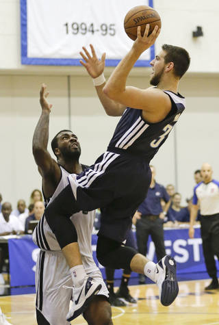 Oklahoma City Thunder's Mitch McGary, right, takes a shot over Brooklyn Nets' Donte Green, left, during an NBA summer league basketball game in Orlando, Fla., Monday, July 7, 2014. (AP Photo/John Raoux)