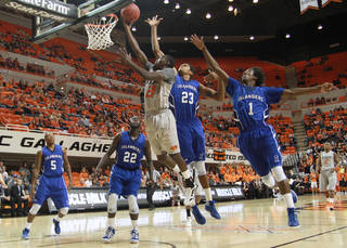 OSU COLLEGE BASKETBALL: Nate Maxey (23) and Hameed Ali (1) try to defend Fred Gulley (21) as he shoots a layup during the game between the Oklahoma State University Cowboys and the Texas A&M Corpus Christi Islanders at Gallagher-Iba Arena in Stillwater, Okla., Friday, Nov. 11, 2011. PHOTO BY MITCH ALCALA, FOR THE OKLAHOMAN. ORG XMIT: KOD