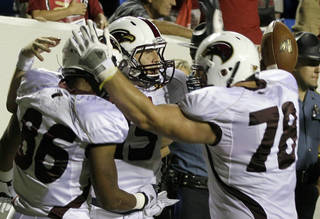 Louisiana Monroe quarterback Kolton Browning, center, celebrates with teammates Je'Ron Hamm (86) and Jon Fisher (78) after Browning scored the winning overtime touchdown to defeat Arkansas 34-31 in an NCAA college football game in Little Rock, Ark., Saturday, Sept. 8, 2012. (AP Photo/Danny Johnston) ORG XMIT: ARDJ110