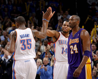 Oklahoma City's Daequan Cook (14) and Kevin Durant (35) celebrate beside Los Angeles' Kobe Bryant (24) during an NBA basketball game between the Oklahoma City Thunder and the Los Angeles Lakers at Chesapeake Energy Arena in Oklahoma City, Thursday, Feb. 23, 2012. Oklahoma City won 100-85. Photo by Bryan Terry, The Oklahoman