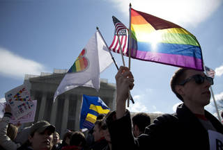 FILE - It is March 27, 2013, file photo Kevin Coyne of Washington holds flags in front of the Supreme Court in Washington as the court hears arguments on gay marriage. Sometime this early July, the Court will announce the outcomes in cases on Californian's ban on same-sex marriage, Proposition 8, and the federal Defense of Marriage Act, the federal law that defines marriage as the union of a man and a woman. (AP Photo/Carolyn Kaster, File)