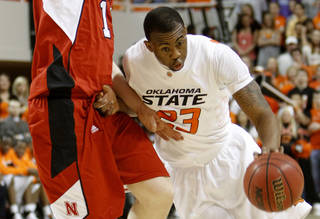 OSU's James Anderson, right, drives past Nebraska's Brandon Ubel . Photo by Doug Hoke, The Oklahoman