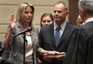"""Ann """"A.J."""" Griffin, Guthrie, takes the oath of office as state senator on Wednesday, April 11, 2012, in Oklahoma City, Okla. Her husband Trey Griffin holds the Bible as Justice Steven Taylor presides. Photo by Steve Sisney, The Oklahoman"""