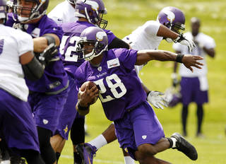 In this photo taken June 18, 2013, Minnesota Vikings running back Adrian Peterson carries the ball during NFL football minicamp at Winter Park in Eden Prairie, Minn. In training camp, an allergic reaction to shellfish caused Peterson to gasp for air as his throat swelled. Vikings staff had epinephrine injections handy, and the star running back was soon out of trouble. Now, Peterson has added EpiPen to his portfolio of sponsorships, grateful for the safety net it provides. (AP Photo/Genevieve Ross) ORG XMIT: MNGR101