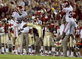 Florida's Rashad Greene (80) catches pass between Oklahoma's Jamell Fleming (32) and Javon Harris (30) on his way to a touchdown during a college football game between the University of Oklahoma (OU) and Florida State (FSU) at Doak Campbell Stadium in Tallahassee, Fla., Saturday, Sept. 17, 2011. Oklahoma won 23-13. Photo by Bryan Terry, The Oklahoman