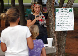 Club leader Monica Wilhoite leads the 4-H pledge during a cookout for Edmond 4-H members at E.C. Hafer Park. PHOTOS BY NATE BILLINGS, THE OKLAHOMAN