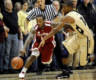 Colorado's Cory Higgins, right, tries to knock the ball from the hands of Oklahoma's Tommy Mason-Griffin during an NCAA basketball game in Boulder, Colo., on Wednesday Feb. 17, 2010. (AP Photo/The Camera, Mark Leffingwell)