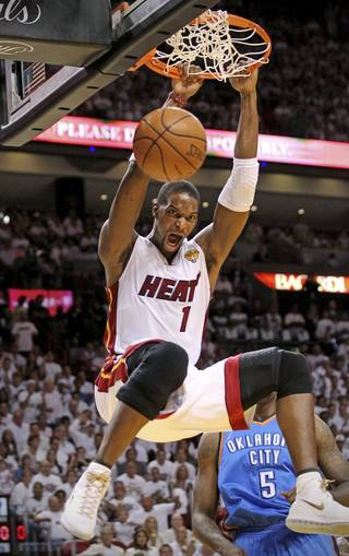 Miami Heat's Chris Bosh (1) dunks past Oklahoma City Thunder's Kendrick Perkins (5) in the first quarter of Game 3 of the NBA Finals basketball series, Sunday, June 17, 2012, in Miami. (AP Photo/The Miami Herald, Al Diaz) MAGS OUT ORG XMIT: FLMIH202