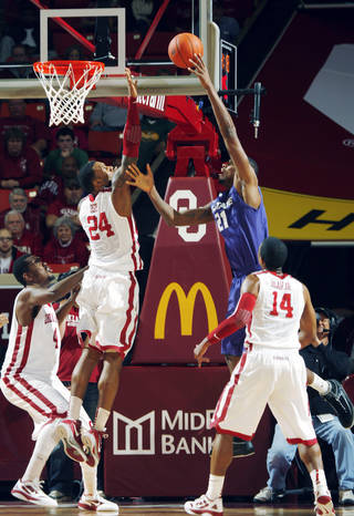 Oklahoma Sooners' Romero Osby (24) blocks a shot by Kansas State Wildcats' Jordan Henriquez (21) in the first half as the University of Oklahoma (OU) Sooners play the Kansas State Wildcats in men's college basketball at the Lloyd Noble Center on Saturday, Jan. 14, 2012, in Norman, Okla. Photo by Steve Sisney, The Oklahoman