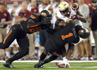 Oklahoma State's Kevin Peterson (1) and Sam Wren (89) tackle Florida State's Karlos Williams (9) during the college football game between Oklahoma State University (OSU) and Florida State University (FSU) at the AdvoCare Cowboys Classic at At&T Stadium in Arlington, Texas, Saturday, Aug. 30, 2014. Photo by Sarah Phipps, The Oklahoman